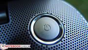 The svelte power button embedded in the perforated speaker cover