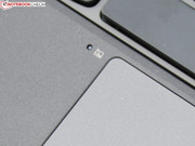 The touchpad is disabled when a hand rests on the sensor beside it.